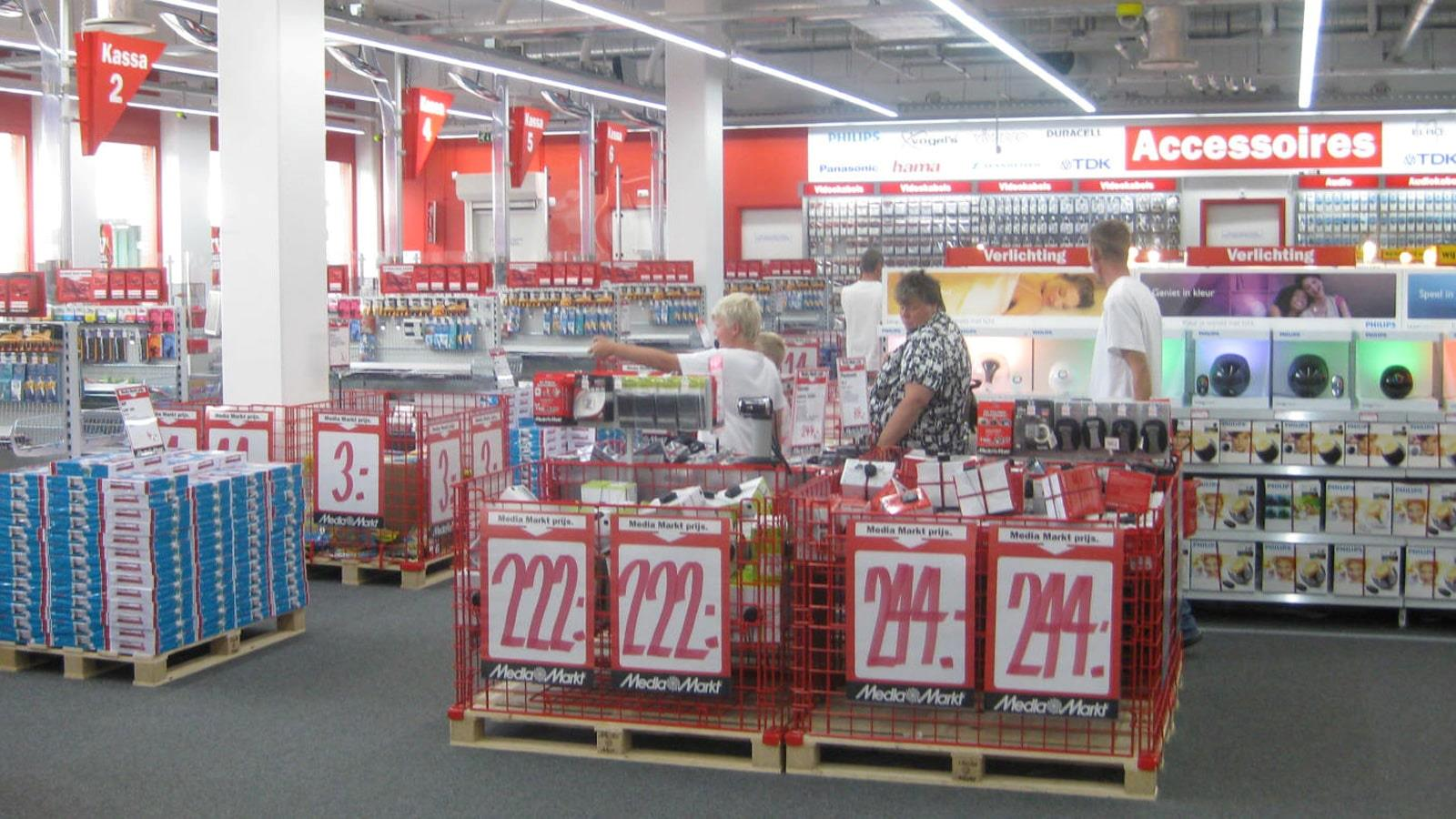 Men and women look at sale goods in Media Markt shop