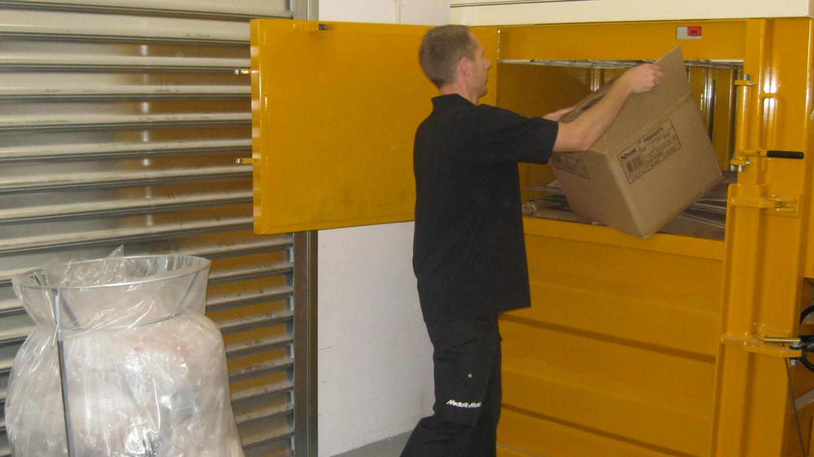 Man from Media Markt throws cardboard boxes into Bramidan baler