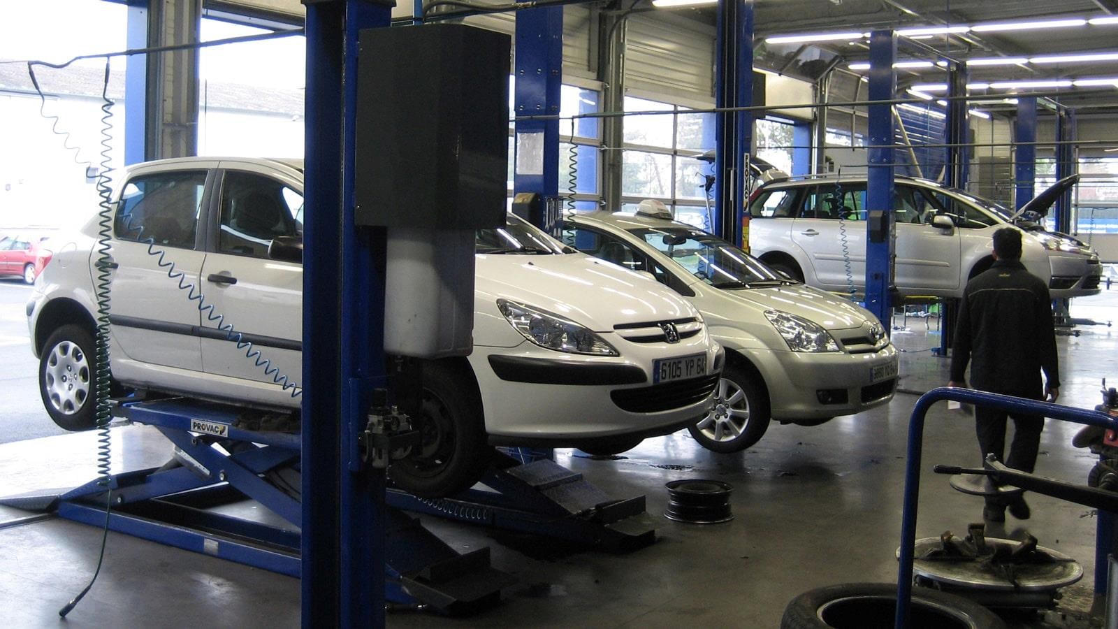 Cars hoisted up for inspection by Norauto mechanics