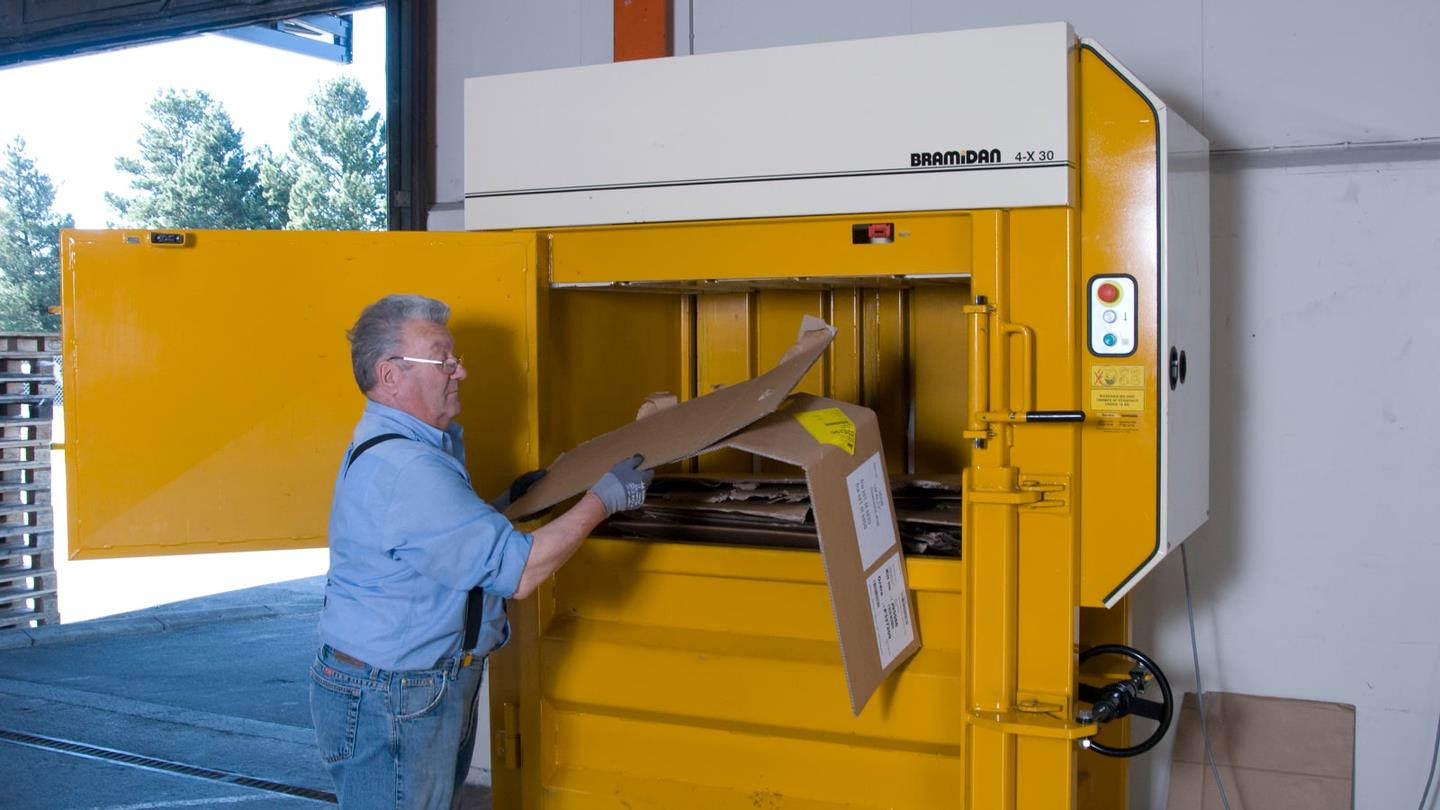Employee at RewAir throws cardboard waste into a Bramidan baler