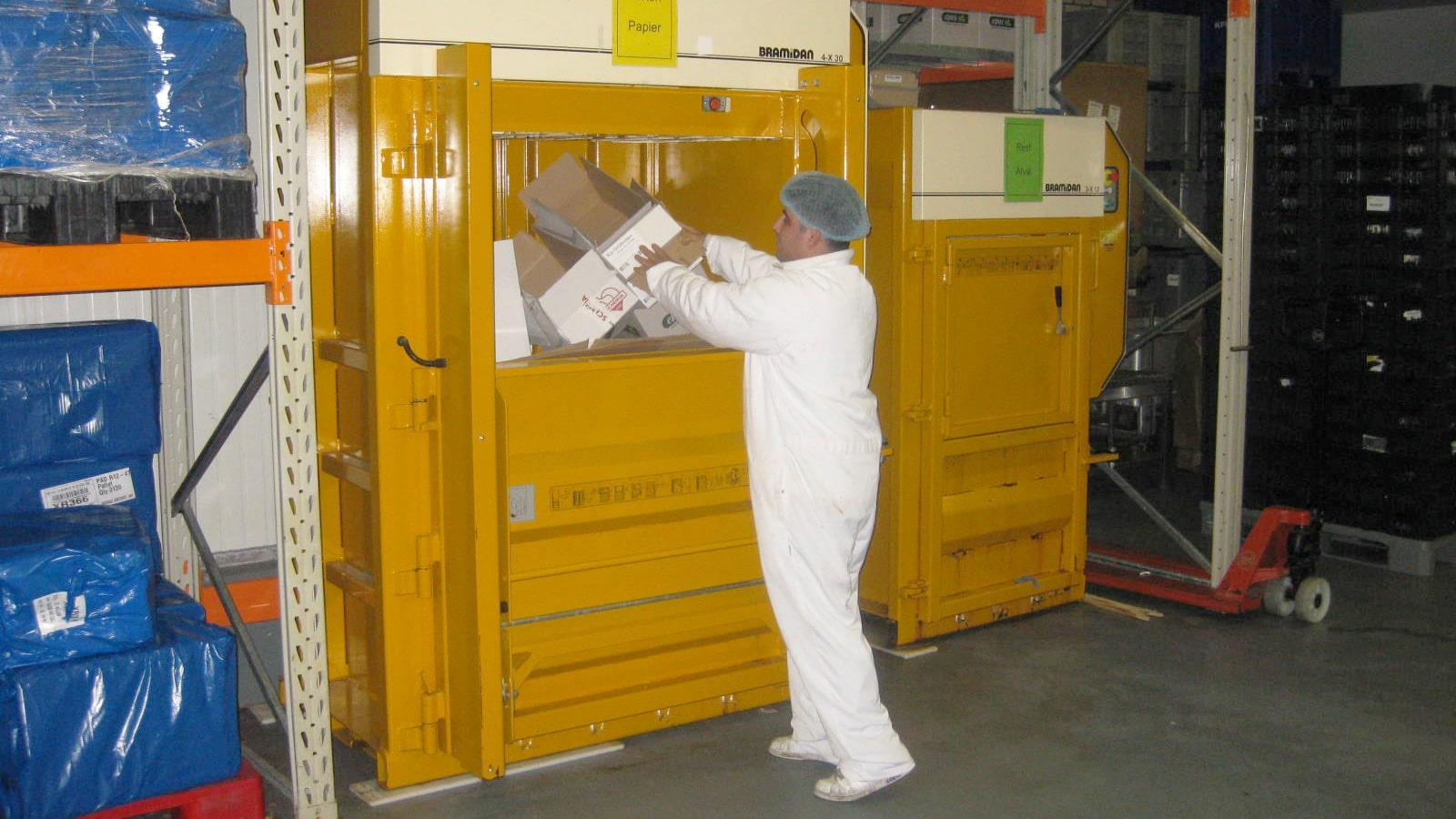 Man in white worksuit compacting cardboard in Bramidan baler