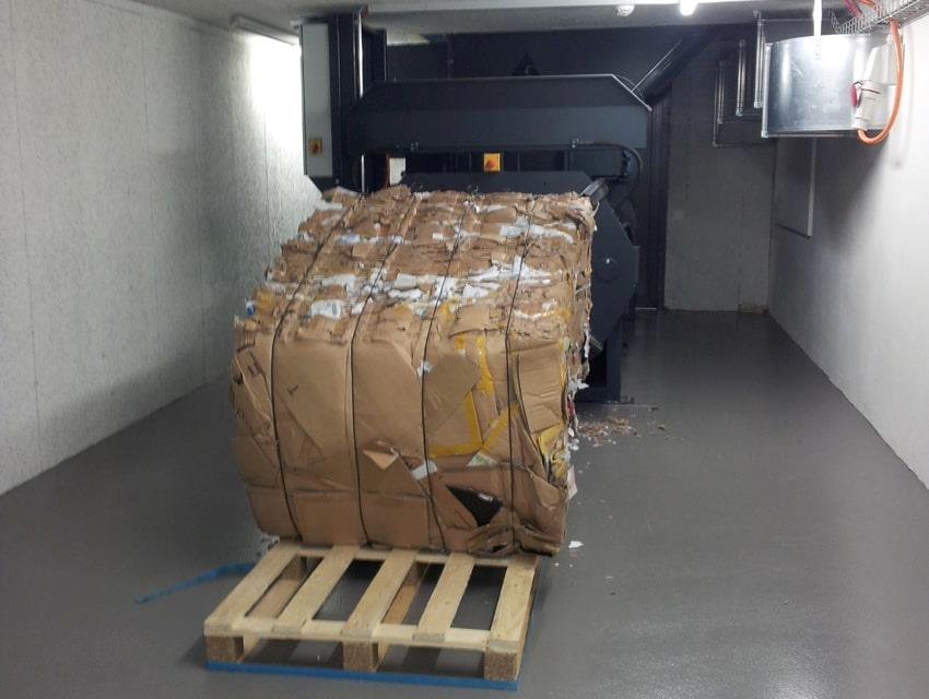 Cardboard bales coming out of horizontal baler onto pallet